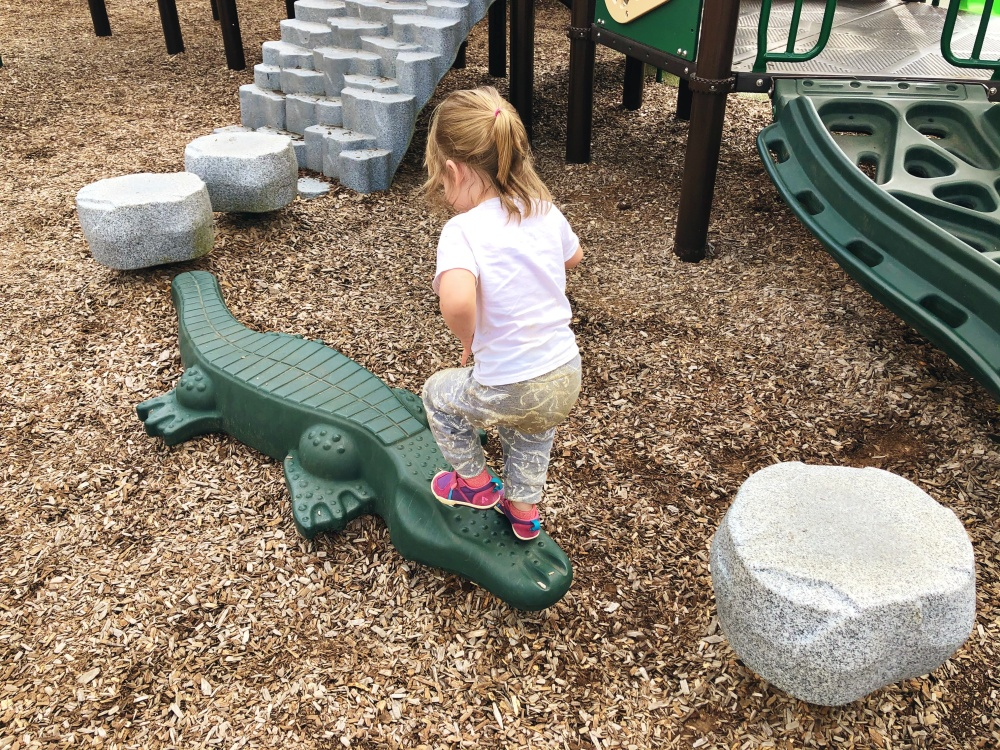 toddler climbing a plastic crocodile near a playscape at Don Fox Community Park in Lebanon, TN