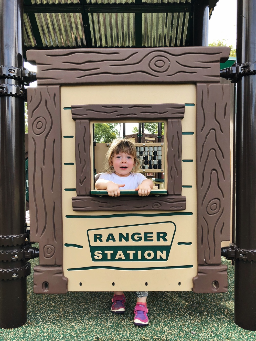 toddler standing at pretend ranger station at Don Fox Community Park in Lebanon, TN