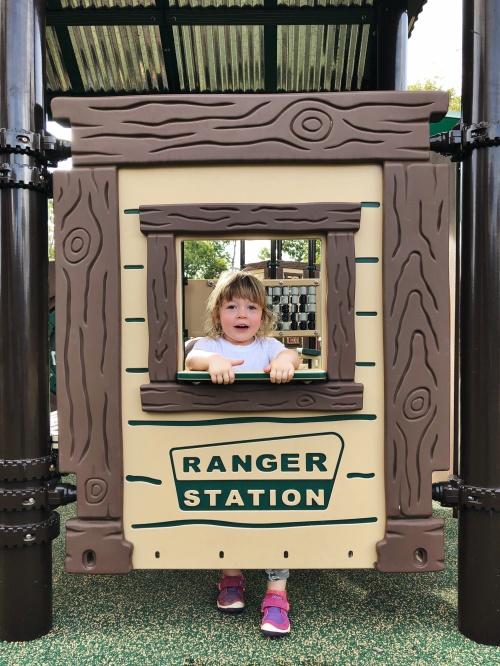 toddler standing at pretend ranger station at Don Fox Community Park in Lebanon, TN