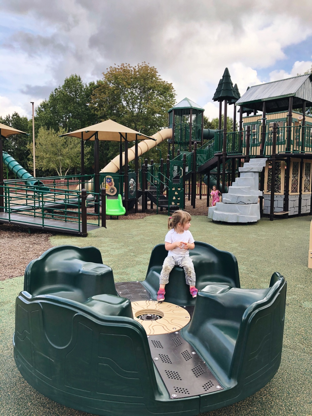toddler sitting alone on a stationary spinning structure at Don Fox Community Park in Lebanon, TN