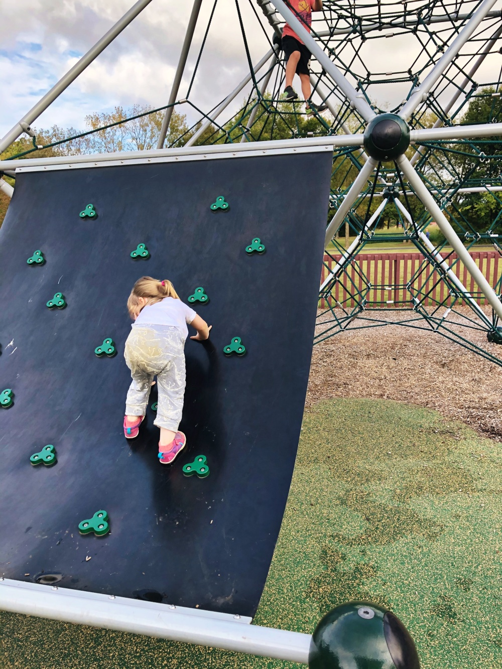 toddler scaling parkour wall near rope climbing structure at Don Fox Community Park in Lebanon, TN