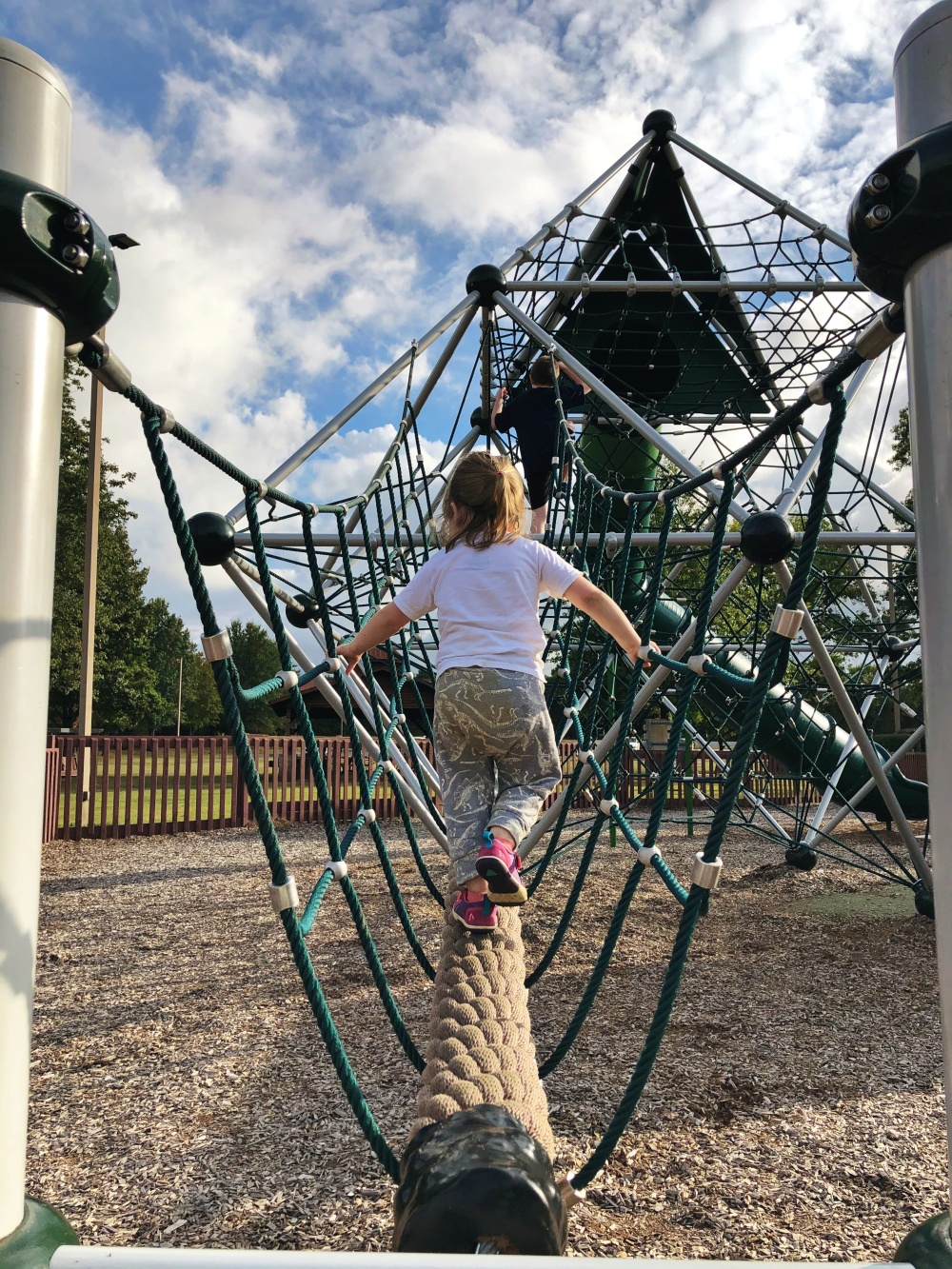 toddler climbing rope bridge to large rope structure to top of large green slide at Don Fox Community Park in Lebanon, TN