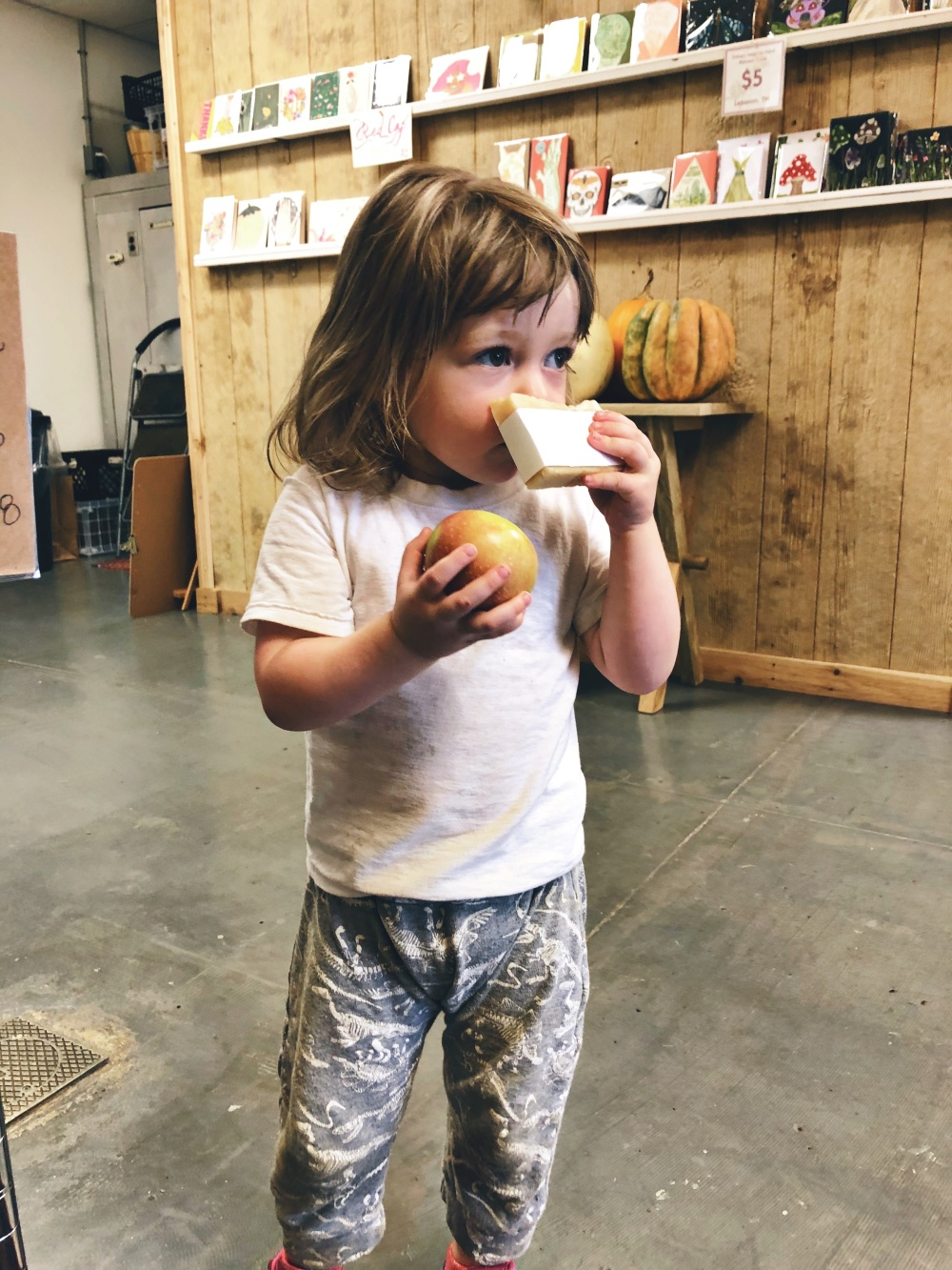 toddler standing in lifestyle grocery store Demeter's Common in Lebanon, TN holding a Rome apple and slice of handmade hand soap